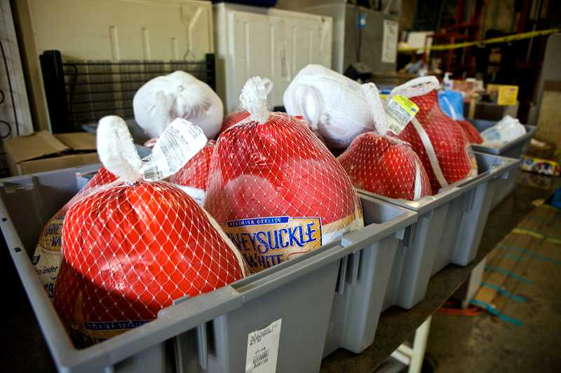 by: TIMES PHOTO: JAIME VALDEZ - Frozen turkeys sit in a bin for people to pick-up at the recently re-located Sunshine Pantry in Beaverton.