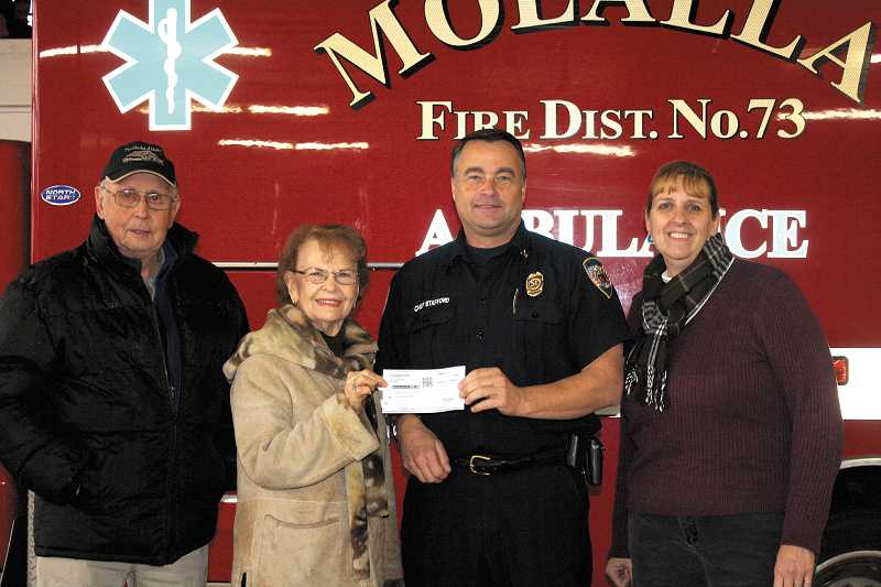 by: PEGGY SAVAGE - Molalla Fire Chief is presented a check by Lorna Wilson from Mulino Hamlet, along with Mr. Wilson and Laurel Roses.