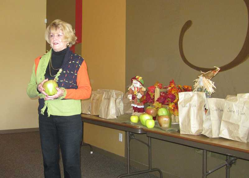 by: BARBARA SHERMAN - APPLE TREATS SERVED AFTER PRESENTATION - Diane Rhodes tells Summerfield Garden Club members how huge apples were discovered in the Hood River area before each guest got to pick up an apple to take home.