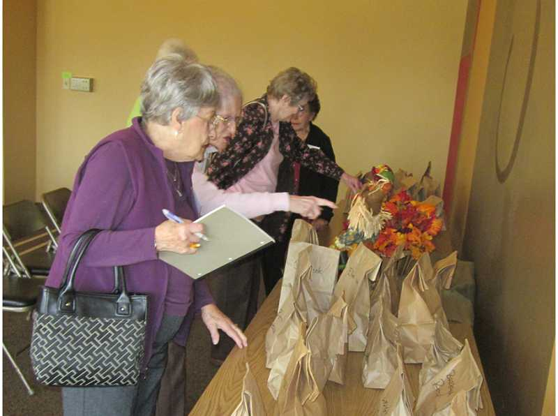 by: BARBARA SHERMAN - TAKING AN APPLE HOME IS PART OF APPLEFEST - Following Diane Rhodes' talk on the origination of the giant Hood River apples, garden club members pick up sacks containing apples to take home.