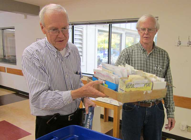 by: BARBARA SHERMAN - MAKING ROOM FOR MORE - Westside Stamp Club President Steve Turner (left) and Andrew Held move boxes of stamps around at the Tigard Senior Center during a recent meeting.