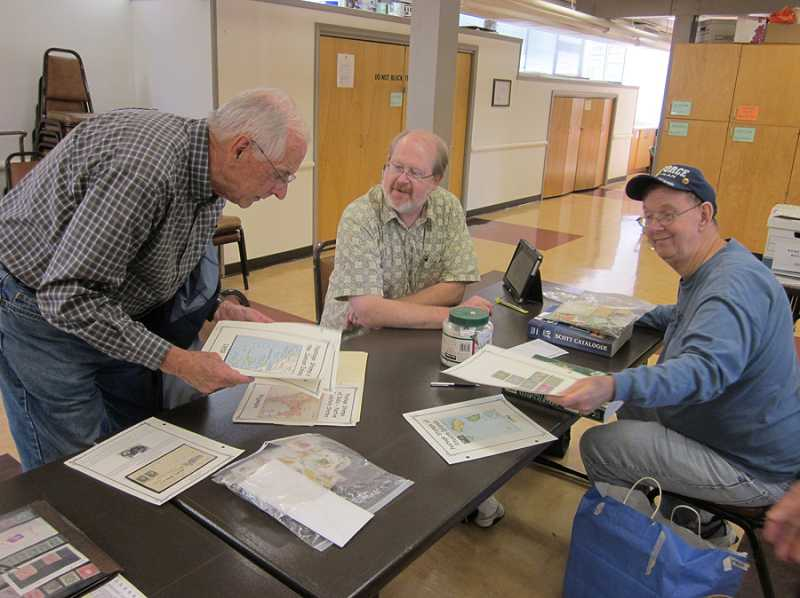 by: BARBARA SHERMAN - ADDING TO THEIR COLLECTIONS - Purusing stamps at a Westside Stamp Club meeting are (from left) Andrew Held, Bill Seymour and Paul Stromberg.