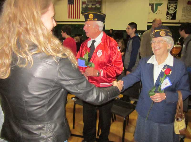 by: BARBARA SHERMAN - APPRECIATION - Following the THS veterans assembly, a woman shakes hands with Patsy Nestor, who lives in Tigard, served during the Korean War in the Women's Army Corps and is active at Tigard American Legion Post 158; beside Nestor is Hank Hess, who lives in Summerfield and served in the Air Force for four years and the Army reserves for two years.