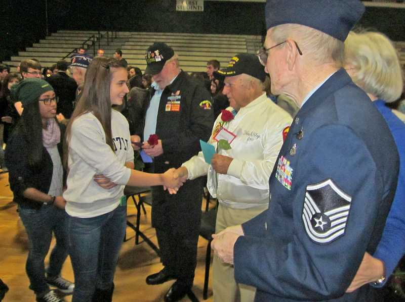 by: BARBARA SHERMAN - GREETING WAR HEROES  - A Tigard High School student shakes hands with Summerfield resident Joseph Doyon, who served in the Navy during World War II, and beside him is Ned Miller of Tigard (with his wife Diane) who served in the Air Force from 1964 to 2000 during the Vietnam and Gulf wars.