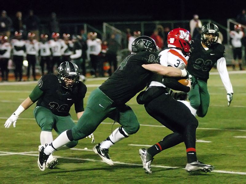 by: DAN BROOD - NO WHERE TO RUN -- North Medford junior quarterback Jacob Moore (3) is surrounded by Tigard's (from left) Jacob Mullen, Jake Biglow and A.J. Hotchkins.