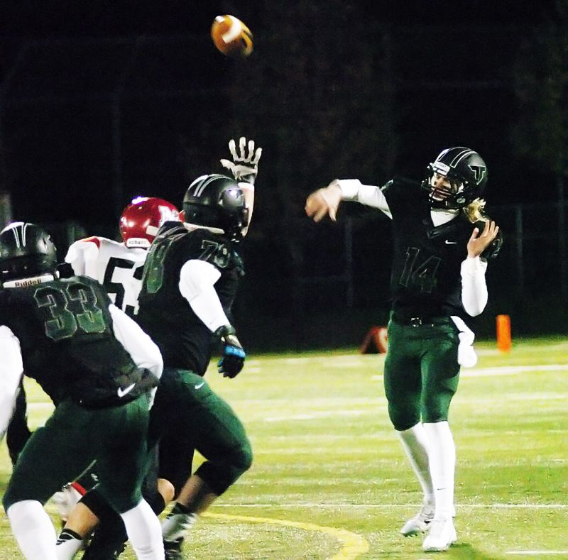 by: DAN BROOD - FLINGING IT -- Tigard High School senior quarterback Jett Even (right) lets the football fly during Friday's state playoff quarterfinal game. Even and the Tigers will play Central Catholic on Saturday.