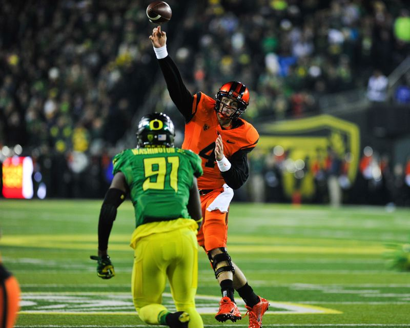 by: COURTESY OF JOHN LARIVIERE - Oregon State's Sean Mannion gets a pass over Oregon defensive lineman Tony Washington.