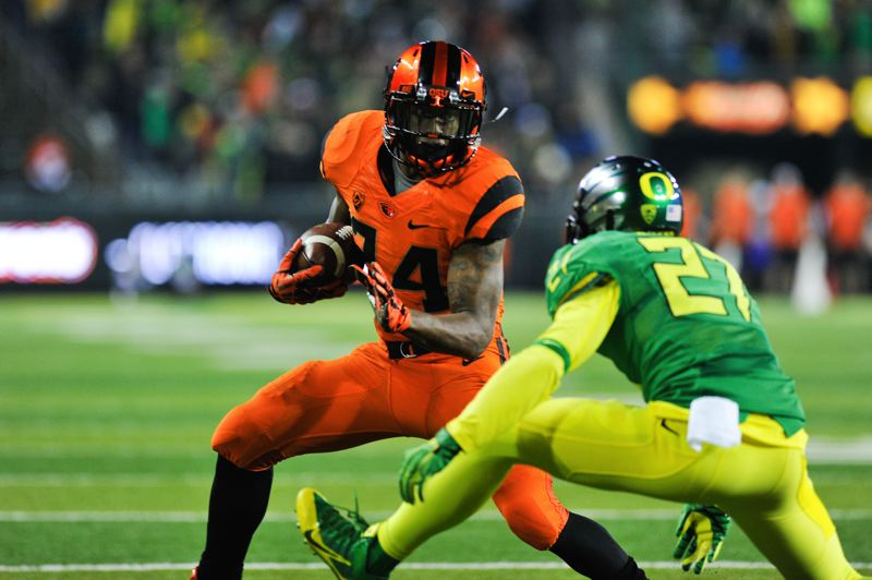 by: COURTESY OF JOHN LARIVIERE - Storm Woods of Oregon State runs past Oregon defensive back Terrance Mitchell.