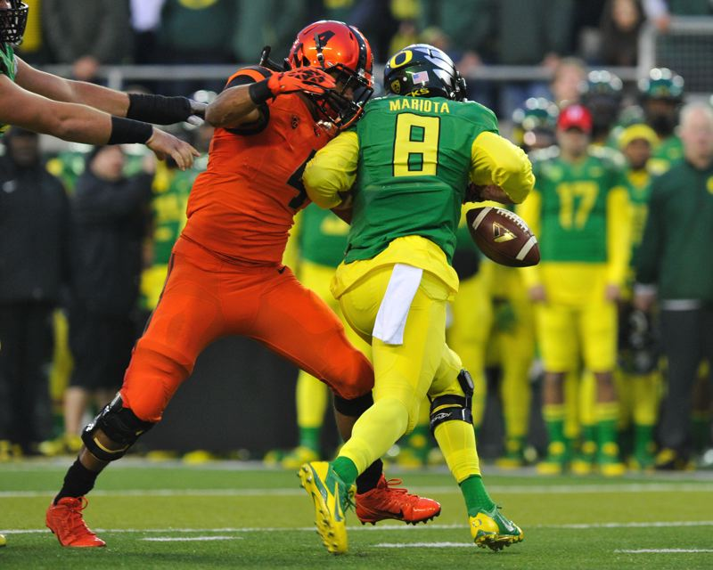 by: COURTESY OF JOHN LARIVIERE - Oregon State's D.J. Alexander forces a fumble as Oregon quarterback Marcus Mariota looks for running room in the first half.