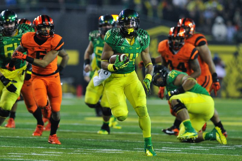 by: COURTESY OF JOHN LARIVIERE - Thomas Tyner picks up 23 yards on a fourth-quarter run for the Ducks.