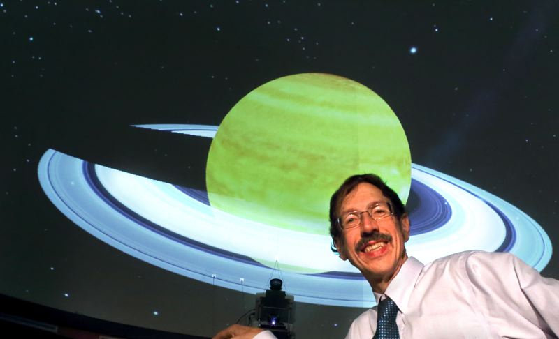 by: CONTRIBUTED PHOTO - A view of Planetarium Director Pat Hanrahan in front of a dome display of Saturn around the sun.