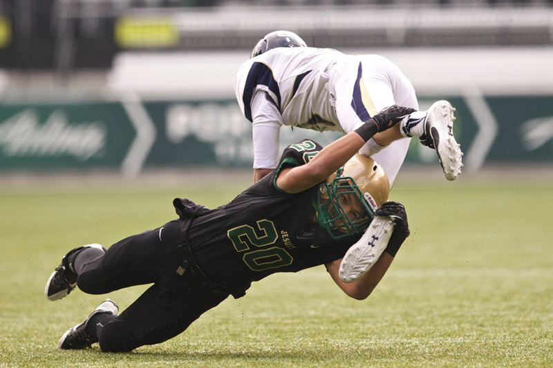 Jesuit defensive back Jordan Happle upends Canby Cougars quarterback Austin Taylor.