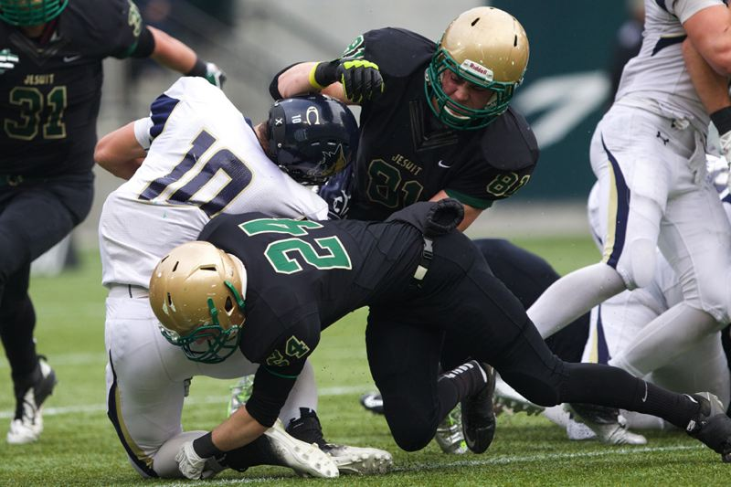 Jesuit's Josh Anderson (24) and Henry Mondeaux tackle Canby's Cole Thompson.