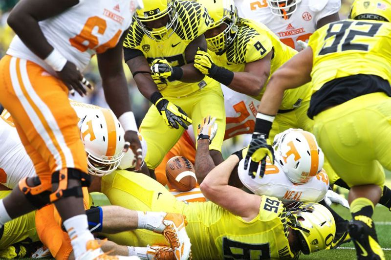 by: TRIBUNE PHOTO: JAIME VALDEZ - Oregon Ducks defensive tackle Taylor Hart (66) strips the ball from Tennessee Volunteers running back Rajion Neal (20) in a game this season.