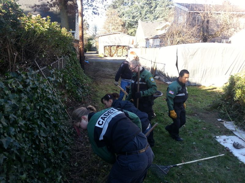 by: PHOTO COURTESY: CCSO - The Clackamas County Sheriff's Office and Hillsboro Police Department cadets team up to rake leaves and clean gutters at the Libke home in Portland.