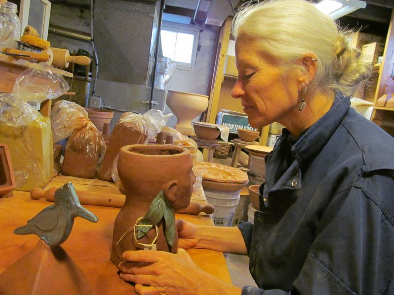 by: PHOTO BY ELLEN SPITALERI - Potter Elizabeth Lee places a label on a head planter; a kingfisher fence-post topper sits to her left.