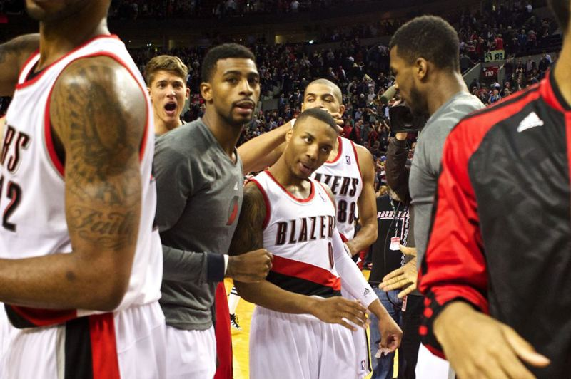 Portland teammates surround guard Damian Lillard during a timeout at Moda Center.