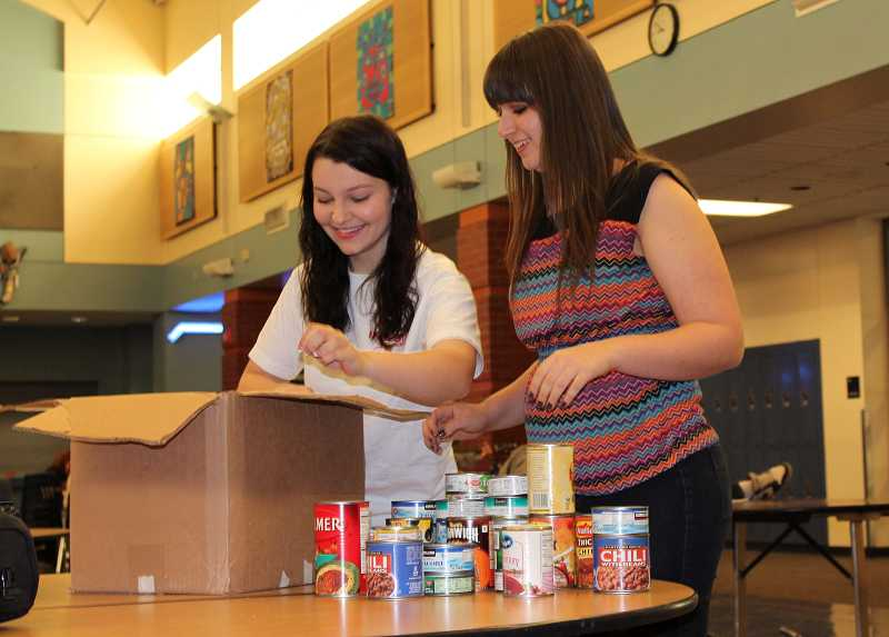 by: SPOKESMAN PHOTO: KATE HOOTS - Wilsonville High School student leaders Justine Cohen, left, and Jessica Small sort through donations in preparation for the schools canned food drive.