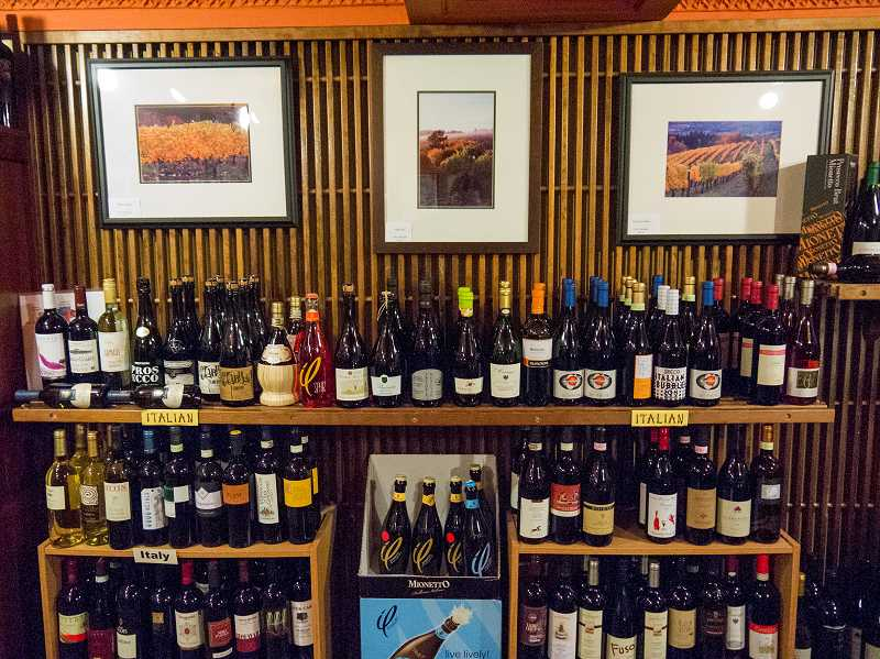 by: NEWS-TIMES PHOTO: CHASE ALLGOOD - Framed art hangs above a display of wine bottles at The Friendly Vine on Main Street.