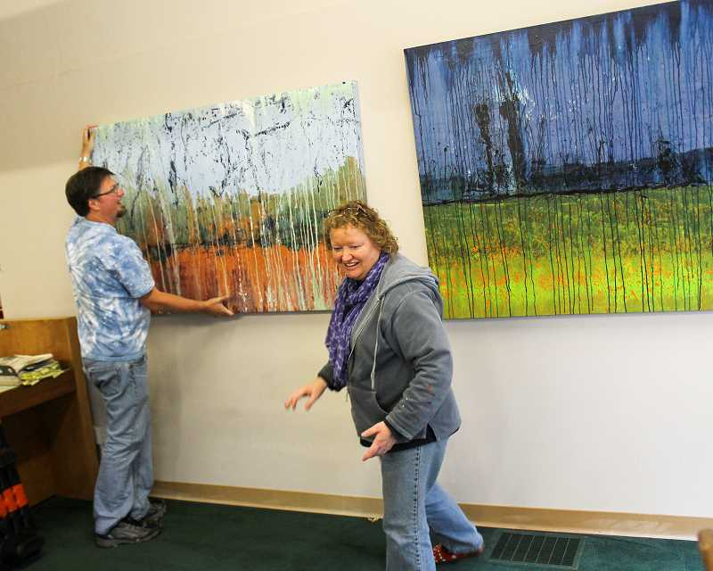 by: NEWS-TIMES PHOTO: CHASE ALLGOOD - Artists Jeffrey Hall and Helvi Smith help hang paintings by  Kathryn Jtineant in the foyer at the News-Times office on Pacific Avenue.