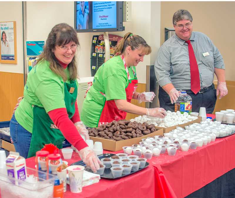 by: RAY HUGHEY - Fred Meyer employees, from left, Debbie Davis, Julie Christ and Kelly Porter hand out doughnuts and beverages to Black Friday to shoppers.