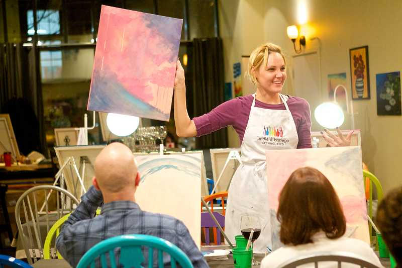 by: TIMES PHOTO: JAIME VALDEZ - Katie Sahnow of Aloha shows her painting to other students during a pop-up art class at The Lounge studio in Northwest Portland.