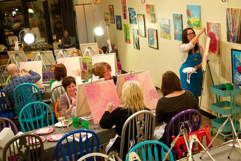 by: TIMES PHOTO: JAIME VALDEZ - Artist Sarah Lopez shows students how to paint a scene during a pop-up art class at The Lounge studio in Portland's Pearl District.
