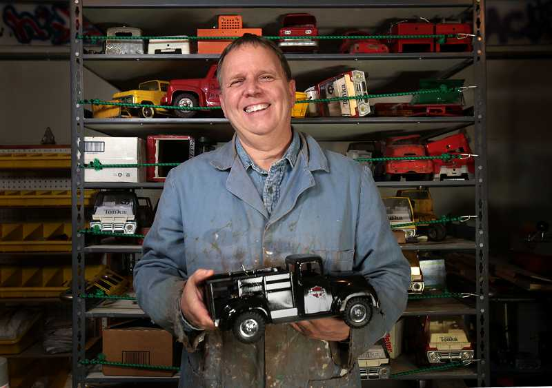 by: JONATHAN HOUSE - John Venheim stands in his garage workshop in Tigard where he refurbishes vintage pressed-steel toy trucks and construction vehicles.