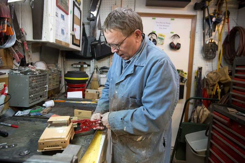 by: TIMES PHOTO: JONATHAN HOUSE - Using a specially devised rivet vice, John Venheim restores an old tin toy truck in his Tigard workshop.