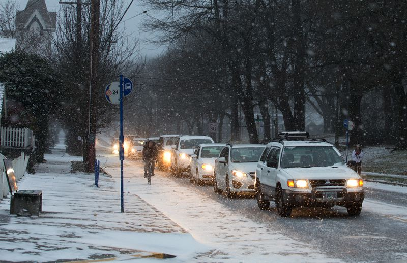 by: TRIBUNE PHOTO: JONATHAN HOUSE - Traffic backed up on Northeast Fremont Street during Friday morning's snowfall.