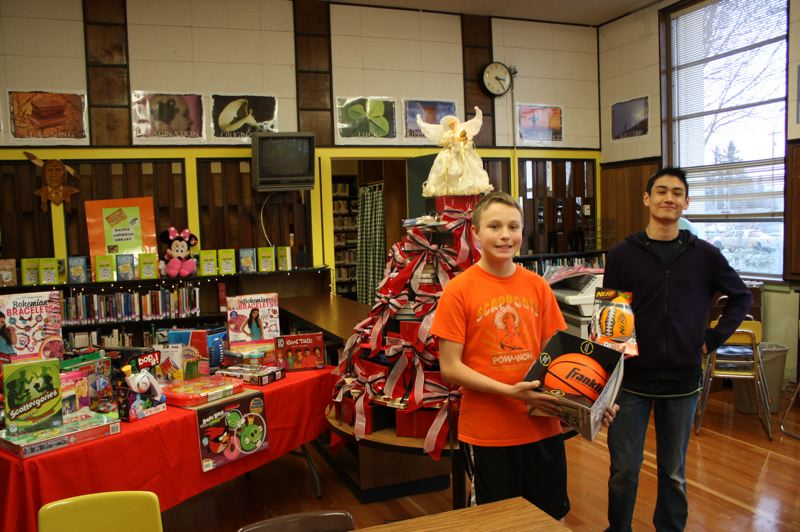 by: SPOTLIGHT PHOTO: ROBIN JOHNSON - Scappoose Middle School eighth-graders Jackson Burum (left) and Zack Dickerson (right), stand next to a decorated tree of books and a table full of toys donated by their peers.