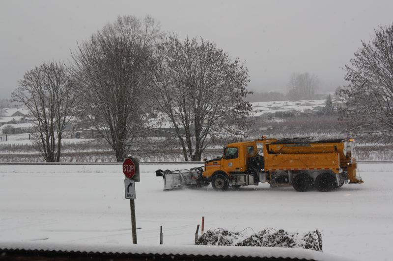by: SPOTLIGHT PHOTO: ROBIN JOHNSON - Snow plow spreads gravel on Highway 30 in Scappoose.
