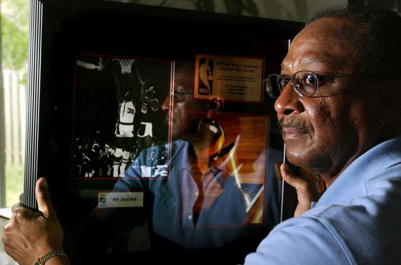 by: TRIBUNE FILE PHOTO: L.E. BASKOW - Lloyd Neal, former Trail Blazers star, looks at a photo of himself on a plaque commemorating his efforts with the 1976-77 NBA championship team.