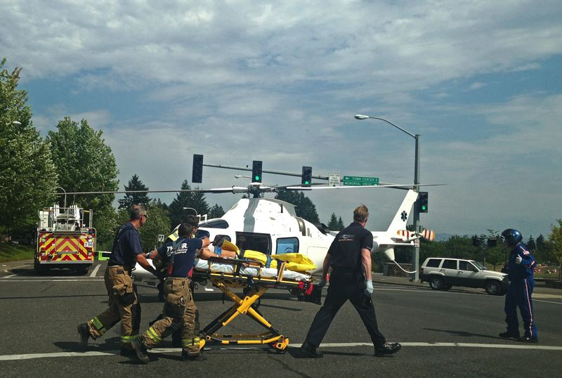 by: COURTESY TUALATIN VALLEY FIRE AND RESCUE - Tualatin Valley Fire and Rescue paramedics wheel one of the two teenage victims of the Aug. 7 crash to a waiting Life Flight helicopter.