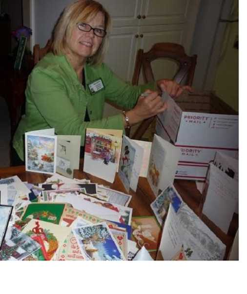 by: SUBMITTED - Mary Reitan, community outreach director for Willson House in Salem and member of Woodburn Immanuel Lutheran Church, packages up Christmas cards to send to service members overseas.