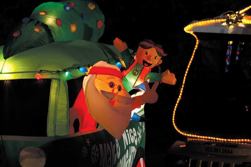 by: PHIL HAWKINS - Golf car decorations can range from simple lights to more elaborate accoutrements, like this inflatable Santa and elf riding in a 60s-era VW bus.