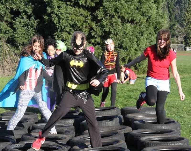 by: SUBMITTED PHOTO - A superhero leads the way through one part of the obstacle course during Athey Creek Middle Schools Turkey Trot fundraiser.