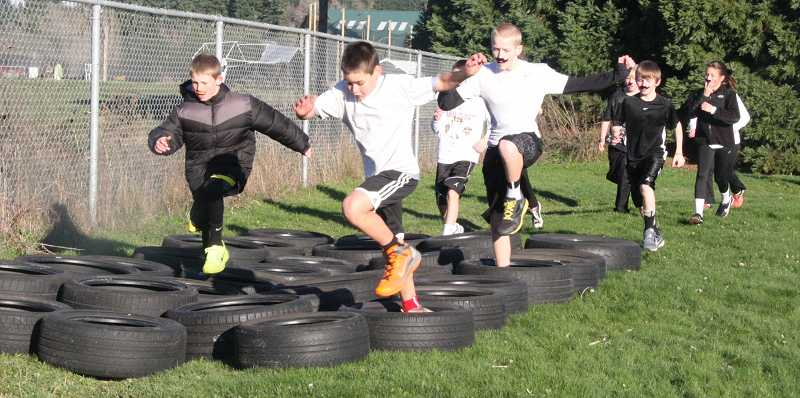 by: SUBMITTED PHOTO - Mustachioed students navigate a tire course at the Athey Creek Turkey Trot on Nov. 22.