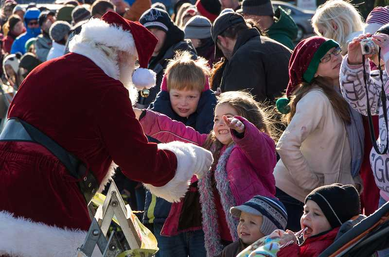 by: GARY BARNES/GTBARNES.COM - A young admirer reacts to Santa's arrival at Sherwood Plaza Shopping Center Dec. 7.