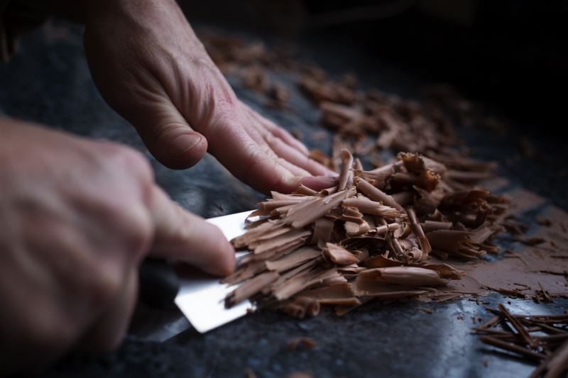 by: TRIBUNE PHOTO: JONATHAN HOUSE - Master Chocolatier Julian Rose makes milk chocolate shavings as a decoration in the test kitchen of Moonstruck Chocolates.