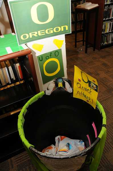 by: TIDINGS PHOTO: VERN UYETAKE - The library held a competition to see which team's food barrel would collect the most food donations.
