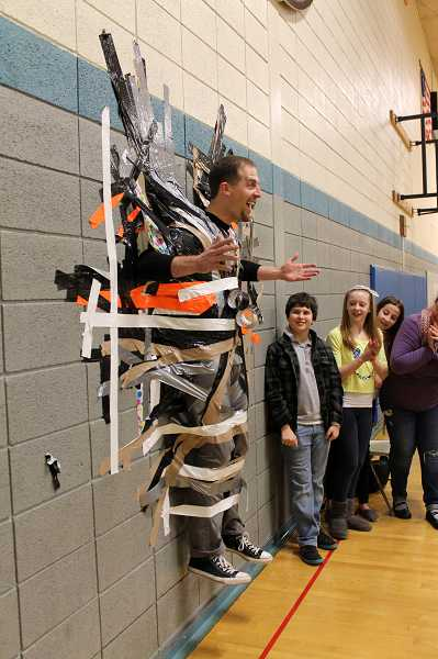 by: REVIEW PHOTOS: JILLIAN DALEY - Lakeridge Junior High Principal Kurt Schultz on Dec. 5 allowed himself to be duct taped to a wall in front of his students, including, from left, Trent Gasparitsch, Nykki Olejniczak and Molly Bradley.