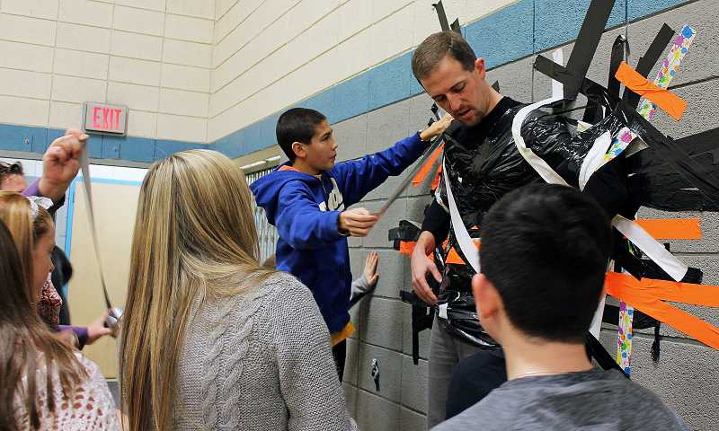 by: REVIEW PHOTO: JILLIAN DALEY - Eighth-grader Brad Myers was one of several people who made sure Kurt Schultz stuck to the wall.