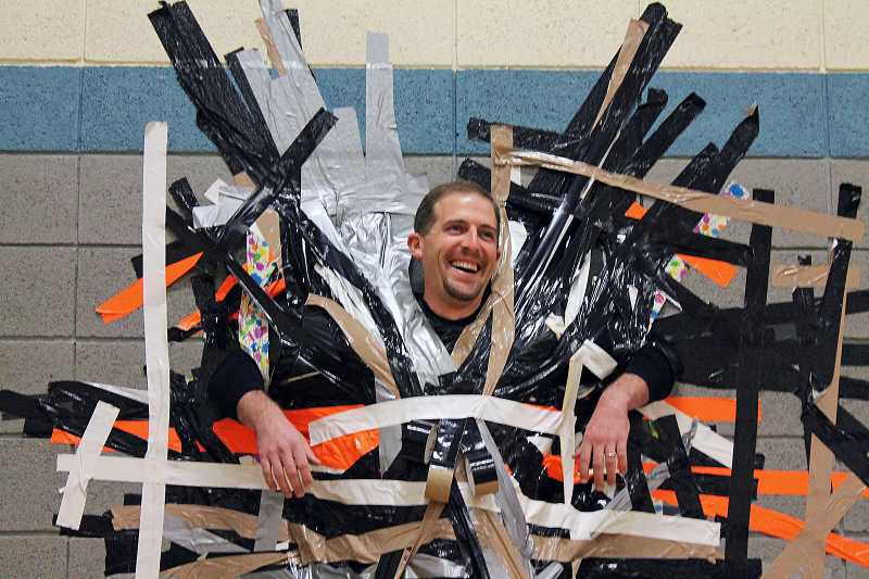 by: REVIEW PHOTO: JILLIAN DALEY - Lakeridge Junior High Principal Kurt Schultz smiled and laughed during most of the duct tape assembly.