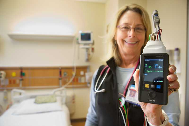 by: JAIME VALDEZ - Nan Beckwith, a registered nurse in the Legacy Meridian Park Medical Center Chest Pain Center, holds a telemetry cardiac monitor.