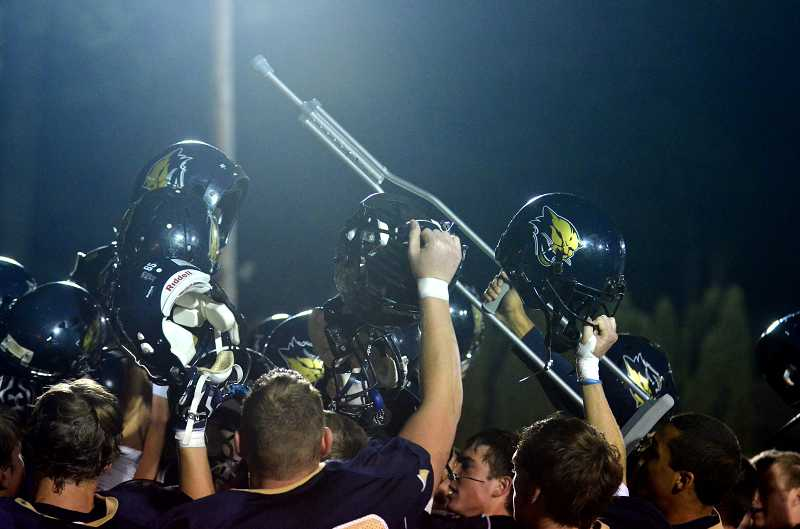 by: JEFF GOODMAN / FILE - Injuries played a large role in the Canby football team's 2013 season. Above, senior linebacker Sam Bodine holds up one of his crutches in a huddle Oct. 18 after the Cougars defeated West Linn.