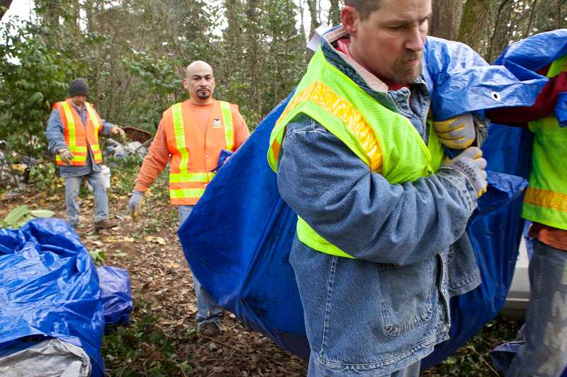 by: TIMES PHOTO: JAIME VALDEZ - Work crews haul bags of debris from the campsite to dumpsters. Police say the property owner Oregon Education Association did not realize the camp was there until police notified them, then asked police to remove it. It will likely take another few days to clear out the rest of the debris, police estimate.