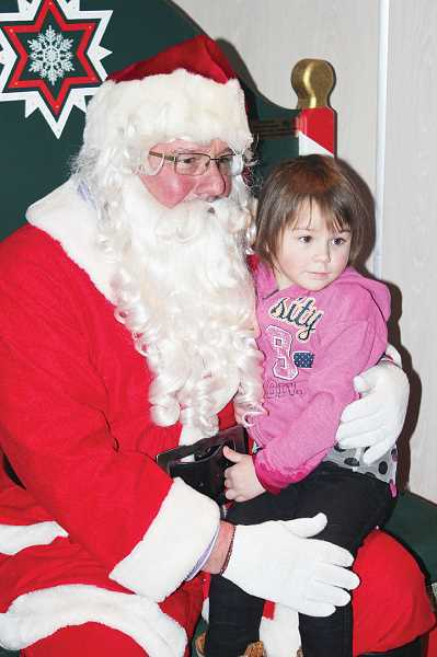 by: HOLLY M. GILL - Zoey Adams, 3, was among dozens of children who had their picture taken with Santa after the parade.