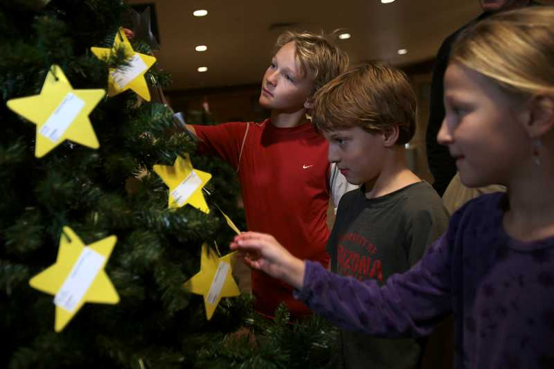 by: TIMES PHOTO: JONATHAN HOUSE - From left, Charles, Ryan and Natalee Mackin check out the family adoption stars on a Christmas tree at Sunset Presbyterian Church. The stars represent families that church members can claim to help chip in for Christmas presents.