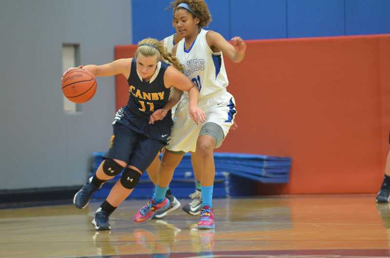 by: JEFF GOODMAN - Senior guard Ashley Evans tries to drive around St. Mary's junior Tasia Bilbrew during the Canby girls basketball team's season opener Dec. 10 in Portland. Evans led the Cougars with 15 points in a 68-57 loss.
